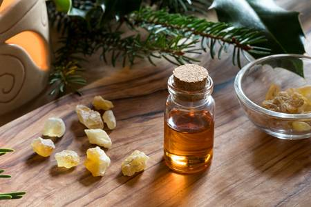 88281102-a-bottle-of-frankincense-essential-oil-with-frankincense-resin-crystals-spruce-and-holly-branches-an